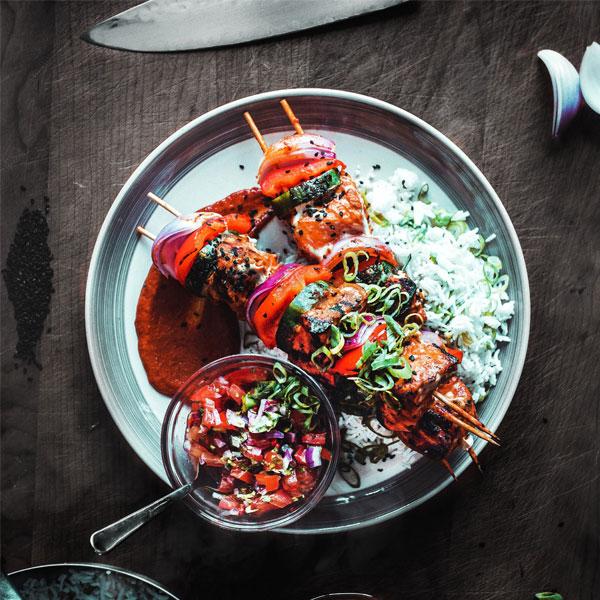 Hähnchenspieße mit Reis und Sauce auf einem Teller