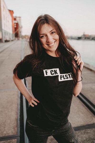 dunkelhaariges Model im FckPlstc Shirt fährt sich mit der Hand durchs Haar