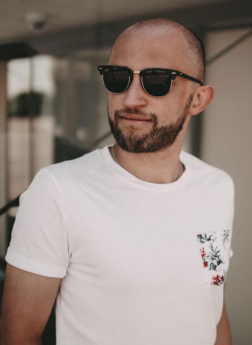 Mann im weißen Shirt und Sonnenbrille schaut cool an der Kamera vorbei